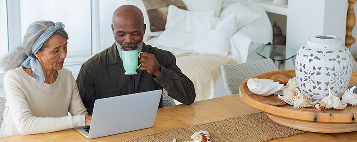 Couple using white laptop on a table while man drinks from a cup
